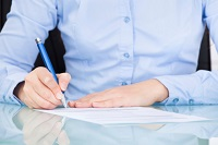 Mann im blauen Hemd sitzt am Tisch und füllt ein Formular aus.