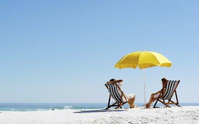 Pärchen am Strand mit gelbem Sonnenschirm