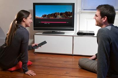 Mann und Frau sitzen mit einer Fernbedienung vor dem Fernseher mit IPTV Entertain der Telekom