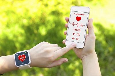 Frau trägt eine Apple Watch und bedient eine Gesundheits-App auf einem iPhone.