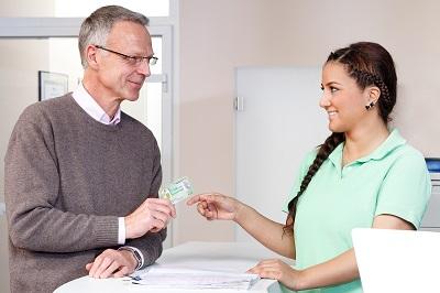 Patient am Empfangstresen mit Gesundheitskarte (Foto: BARMER GEK)
