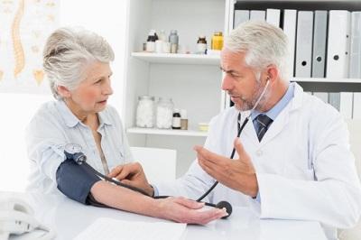 Hausarzt misst Patientin den Blutdruck