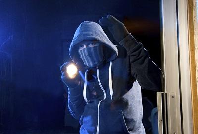 Einbrecher steht mit einer Taschenlampe an einer Wohnungstür und blickt hinein.