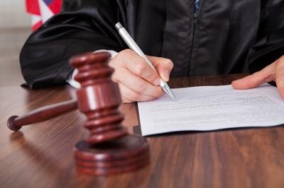 Ein Richter in Robe schreibt ein Urteil am Richtertisch.
