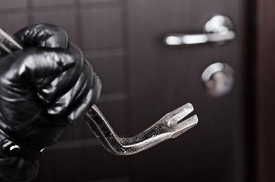 Einbrecher mit Brecheisen an Tür