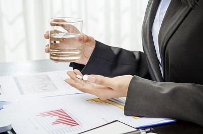 Pillen mit Wasserglas vor Schreibtisch