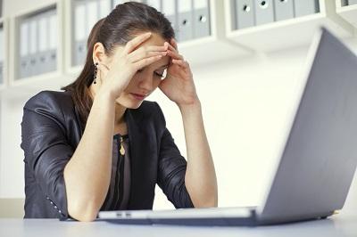 Gestresste Angestellte vor ihrem Laptop