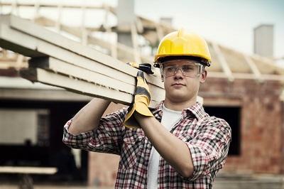 Bauarbeiter mit Helm trägt Holzlatten