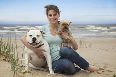 Eine Fraus sitzt am Strand und umarmt eine Bulldogge und einen Yorkshire-Terrier.