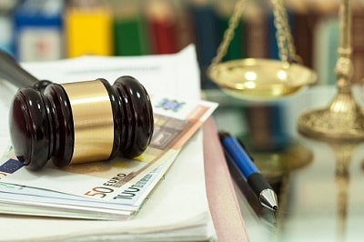 Ein Richterhammer liegt auf Unterlagen und Geldscheinen.