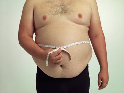 Mann mit Übergewicht und Maßband