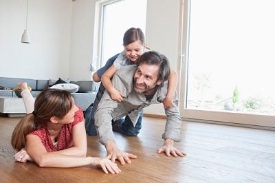 Vater und Mutter spielen im Wohnzimmer mit Kind