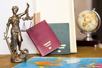 Justitia neben Landkarte und Reisepässen