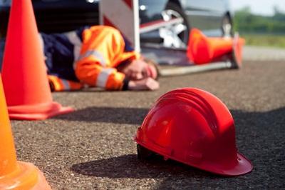 Helm und liegender Bauarbeiter im Hintergrund