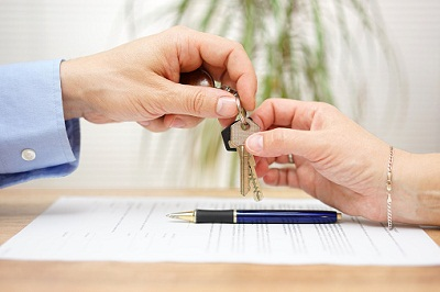 Hände über Vertrag bei Schlüsselübergabe