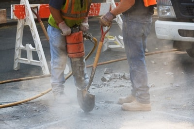 Zwei Straßenarbeiter bei der Arbeit.