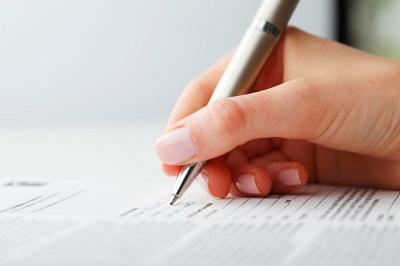 Frauenhand mit Stift und Formular