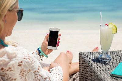 Frau-Smartphone-Strand-Cocktail-Urlaub