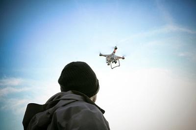 Mann und Drohne am Himmel
