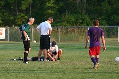 Spieler kümmern sich um verletzten Fußballer.