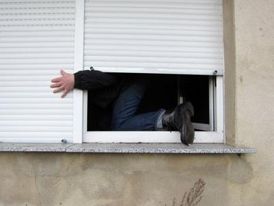 Mann klettert am Fenster
