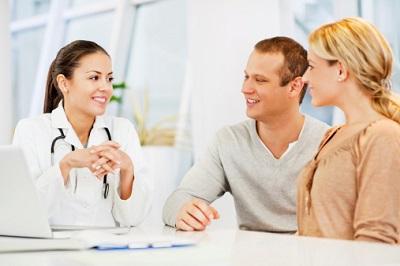 Ärztin spricht mit jungem Paar.