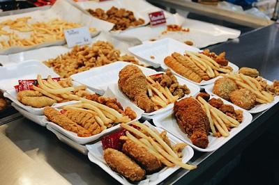 Teller mit Fast-Food-Gerichten sind auf einem Tisch ausgestellt.