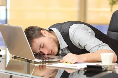 Angestellter schläft im Büro vor dem Laptop