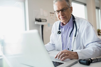 Arzt am Schreibtisch mit Laptop
