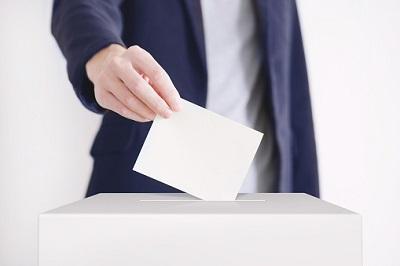 Mann steckt seinen Stimmzettel in eine Box.