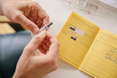 Hand hält Impfdosis mit Impfpass im Hintergrund