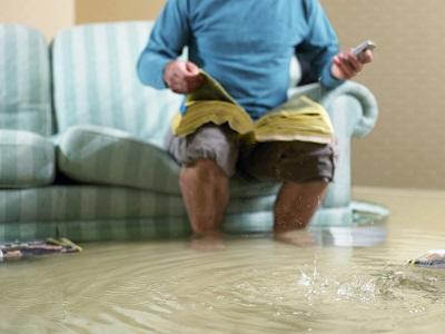 Mann auf Couch bei Hochwasser