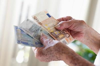 Die Hände einer Seniorin halten Geldscheine.