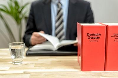 Anwalt mit deutschen Gesetzestexten am Schreibtisch