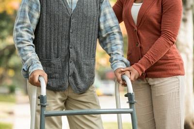 Senior geht mit Hilfe einer Pflegerin an einem Rollator.