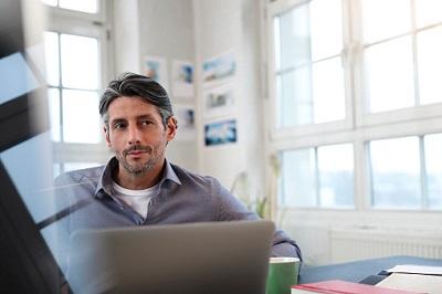 Mann im Büro vor einem Laptop