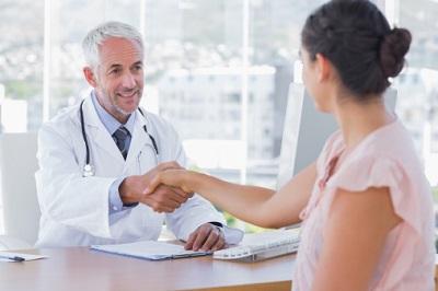 Arzt und Patientin schütteln sich die Hände