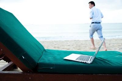 Ein Laptop liegt am Strand, im Hintergrund läuft ein Geschäftsmann.