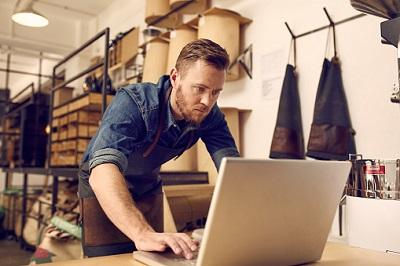 Ein junger Selbstständiger blickt ernst in einen Laptop.