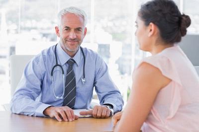 Ein Arzt lächelt während er mit einer Patientin spricht.