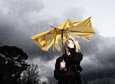 Frau mit kaputtem Schirm im Regen
