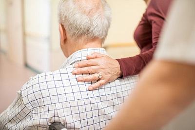 Älterer Mann im Rollstuhl - Eine Frau legt Hand auf den Rücken