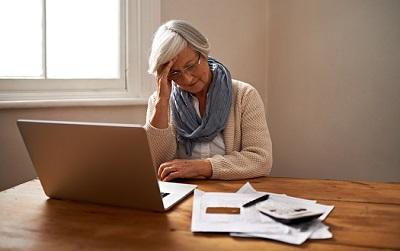 Eine Seniorin sitzt vor einem Laptop und hat Geldsorgen.