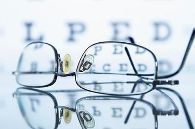 Brille mit Buchstaben im Hintergrund