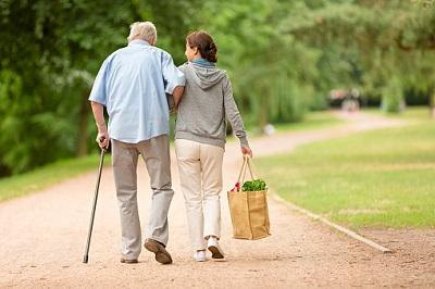 Senior geht mit junger Frau, die eine Einkaufstüte trägt, spazieren.