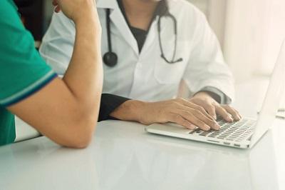 Patient mit Arzt im Gespräch am Tisch