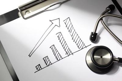 Ein Diagramm zeigt einen positiven Verlauf, ein Stethoskop liegt daneben.