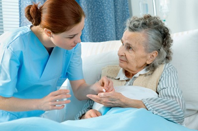 Krankenschwester gibt Seniorin Medikamente