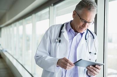 Ein Arzt im Krankenhaus schaut auf ein Tablet.