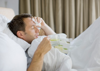 Kranker Mann (mit Grippe) im Bett